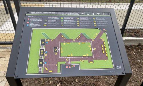 stół z tyflografiką prezentuje schemat obiektów w ogrodzie sensorycznym z opisami w języku braila